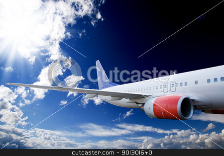 Airplane in Sky stock photo, An airplane flying in the sky against a dramatic background by Tyler Olson