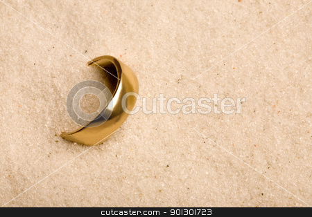 Wedding Ring in Sand stock photo, A wedding ring buried in the sand - lost by Tyler Olson