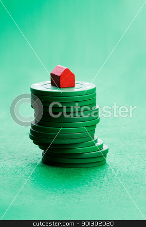 Housing Market Gabmle stock photo, Casino chips with toy house - housing market gamble concept by Tyler Olson