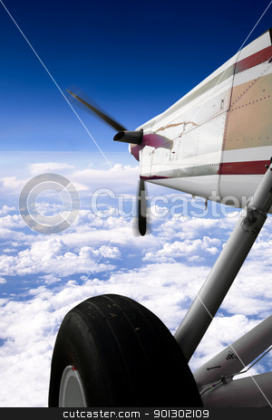Small Airplane in Flight stock photo, A small airplane in flight over clouds by Tyler Olson