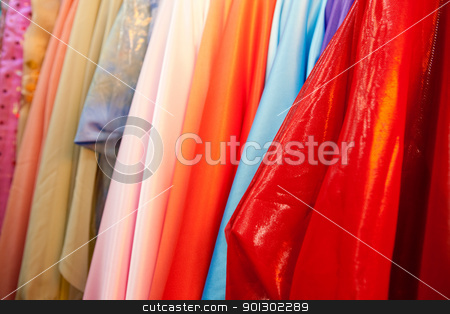 Cloth Background stock photo, A bulk collection of silk cloth hanging on rolls by Tyler Olson