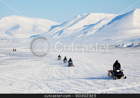 Snowmobile Travel stock photo, A group of snowmobiles on the ice outside Longyearbyen, Svalbard Norway by Tyler Olson