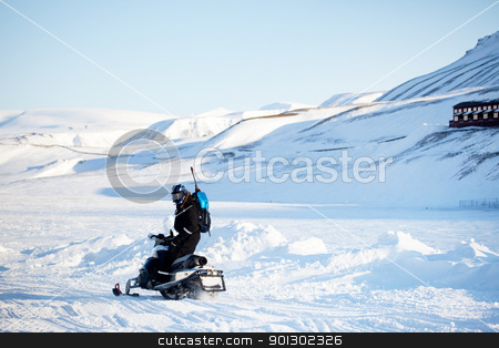 Snowmobile Transport stock photo, A man on a snowmobile with a gun and shovel for safety by Tyler Olson