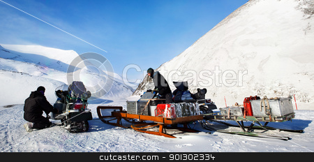 Polar Expedition stock photo, People preparing snowmobiles for an expedition through through winter conditions by Tyler Olson