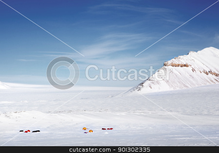 Winter Wilderness Expedition stock photo, A winter wilderness expedition on a mountain landscape, tents in the distance by Tyler Olson