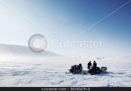 Snowmobile Winter Landscape stock photo, Three snowmobiles on a winter landscape with blowing snow by Tyler Olson