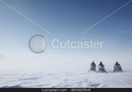Snowmobile in Storm stock photo, Three snowmobiles on a blowing barren winter landscape by Tyler Olson