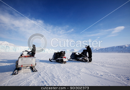 Glacier Expedition stock photo, Three snowmobiles in front of a glacier, Svalbard, Norway by Tyler Olson
