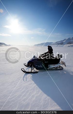 Snowmobile stock photo, A snowmobile on frozen ice on a barren winter landscape by Tyler Olson
