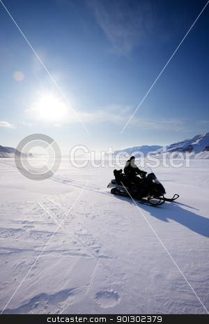 Snowmobile Silhouette stock photo, A snowmobile on frozen ice on a barren winter landscape by Tyler Olson