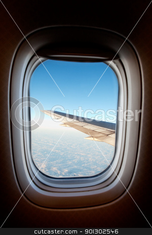 Airplane window  stock photo, An airplane window with wing and cloudscape by Tyler Olson