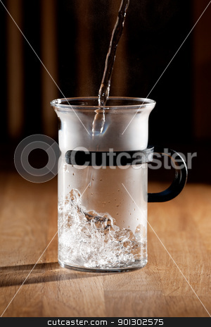Morning Tea stock photo, Early morning tea - glass being filled with water with strong directional light by Tyler Olson