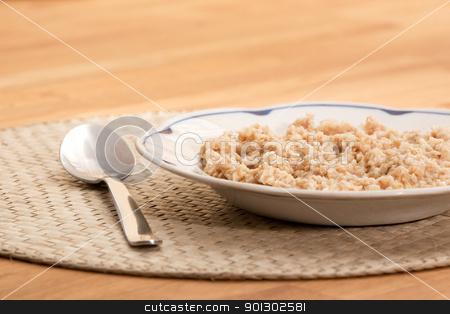 Bowl of Porridge stock photo, A bowl of porridge on a table with a spoon; by Tyler Olson