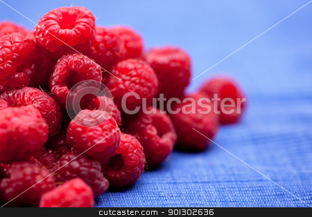 Raspberries stock photo, Fresh raspberries isolated on a blue cloth by Tyler Olson