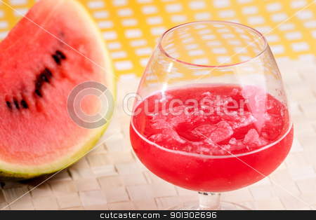 Watermelon Juice stock photo, A red watermelon drink on a picnic table by Tyler Olson