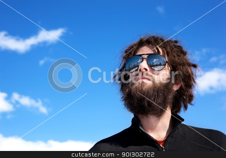 Male Adventurer stock photo, A male with a full beard and retro sunglasses standing in a winter landscape ready for adventure by Tyler Olson