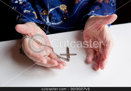 Faith stock photo, A pair of old hands and a cross - shallow depth of field with focus on the cross by Tyler Olson