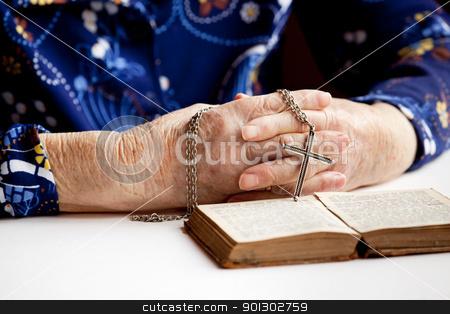 Prayer stock photo, An elderly pair of hands holding a cross by Tyler Olson