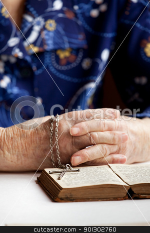 Old Faith stock photo, An old pair of hands with a book and cross - shallow depth of field with focus on cross by Tyler Olson