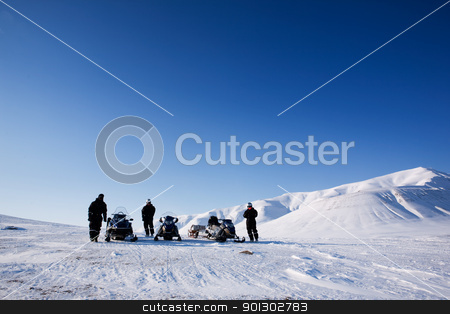 Snomobile Adventure stock photo, Three people with snowmobiles in an arctic landscape by Tyler Olson