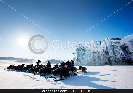 Glacier Tour stock photo, A number of snowmobiles near a glacier in Svalbard, Norway by Tyler Olson