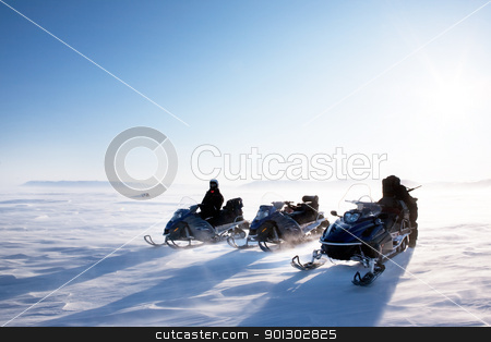 Snowmobile Winter stock photo, A winter landscape with blowing snow and three snowmobiles. by Tyler Olson