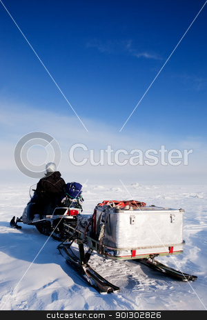Man with Snowmobile stock photo, A man sitting on a snowmobile on a barren snow landscape by Tyler Olson