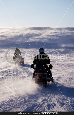 Winter Travel stock photo, Two people riding up a hill on snowmobiles by Tyler Olson
