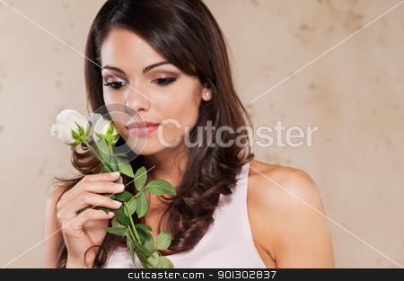 Pretty young woman holding a white rose stock photo, Thoughtful pretty young woman holding a white rose by Tyler Olson