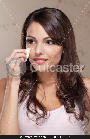 Woman applying face foundation on her face stock photo, Beautiful young woman applying face foundation on her face by Tyler Olson