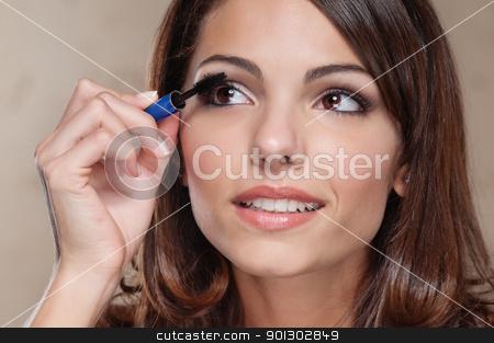 Woman applying mascara on her eyelashes stock photo, Attractive young woman applying mascara on her eyelashes by Tyler Olson