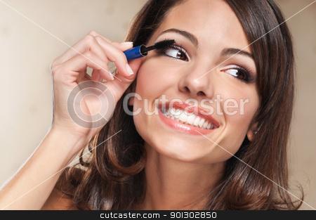 Woman applying mascara stock photo, Beautiful smiling woman applying mascara on her eyelashes by Tyler Olson