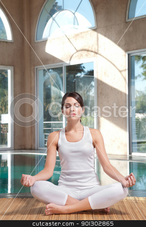 Young woman doing yoga exercise stock photo, An attractive young woman with eyes closed doing yoga exercise on mat by Tyler Olson