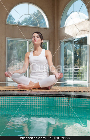 Woman meditating sitting in lotus position stock photo, Young woman meditating sitting in lotus position by Tyler Olson