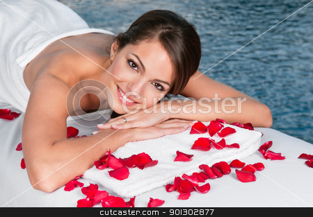 Woman lying on bed in spa stock photo, Portrait of beautiful young female lying on massage bed with rose petals in foreground by Tyler Olson