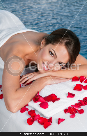 Woman with rose petals lying on bed stock photo, Beautiful young woman lying on massage bed with rose petals in foreground by Tyler Olson
