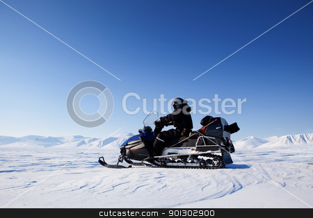 Snowmobile Winter Landscape stock photo, A snowmobile on a frozen lake against a winter landscape with mountains by Tyler Olson