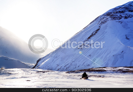 Polar Expedition stock photo, A snowmobile on a beautiful winter mountain landscape by Tyler Olson