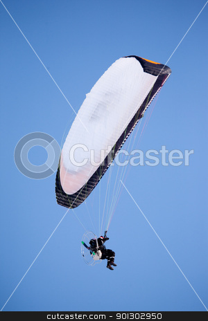 Paraglider  stock photo, A paraglider isolated against a deep blue sky by Tyler Olson
