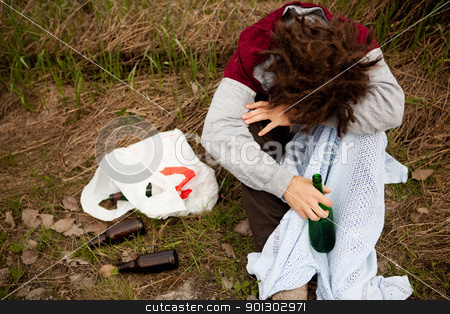 Drunk Person stock photo, A drunk person sitting in a ditch with a wine bottle by Tyler Olson