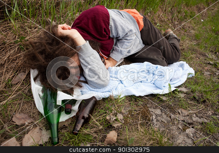 Drunk Passed Out stock photo, A drunk passed out in the ditch with a bunch of alcohol bottles by Tyler Olson