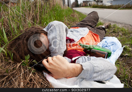 Homeless man stock photo, A homeless drunk person laying by the edge of the road by Tyler Olson