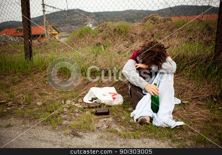 Drunk Homeless Man stock photo, A homeless person sleeping in the ditch by Tyler Olson