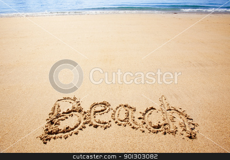 Beach Sand stock photo, Beach written in the sand on the coast with mountains in the background by Tyler Olson