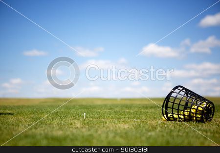 Driving Range stock photo, A tee and yellow golf balls on a driving range by Tyler Olson