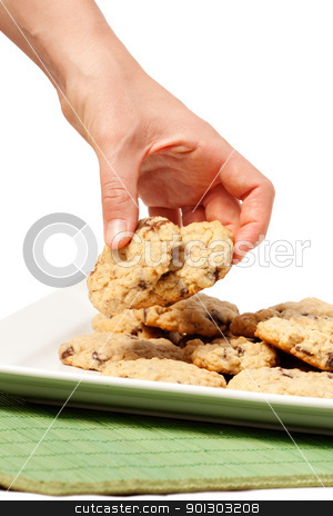 Cookie Temptation stock photo, A plate of oatmeal chocolate chip cookies with a hand taking two. by Tyler Olson