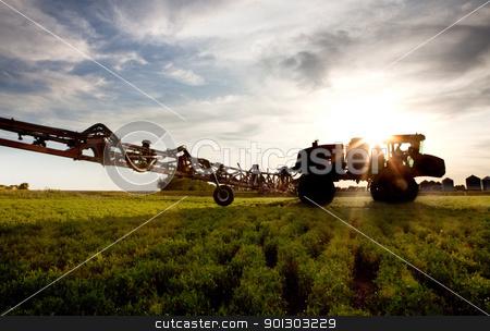 High Clearance Sprayer stock photo, A silhouette of a high clearance sprayer on a field by Tyler Olson