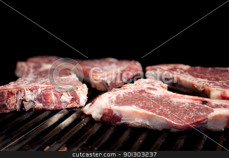 Raw Steak stock photo, Raw steaks on a grill with shallow depth of field by Tyler Olson