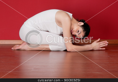 Young woman in a exercise clothing in a yoga pose stock photo, Pretty young woman in a exercise clothing in a yoga pose on floor by Tyler Olson