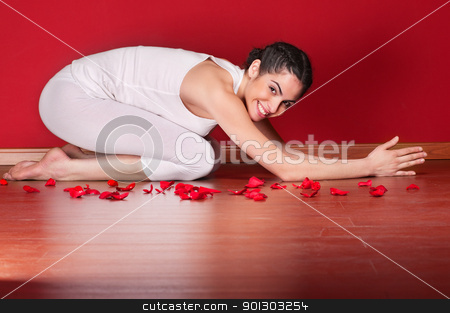 Young female doing yoga in a child pose stock photo, Portrait of a cute young woman doing yoga in a child pose near rose petals by Tyler Olson